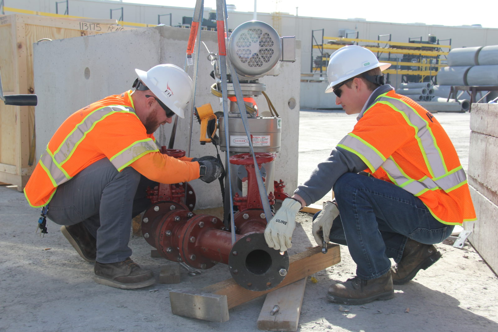 Jensen Water Resources team members install a piping for a packaged grinder vault system to protect a Walmart pump station